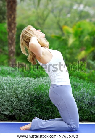 mature woman doing yoga position outside in the garden