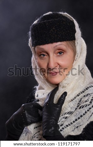 Mature woman dressed in winter clothes and white shawl.