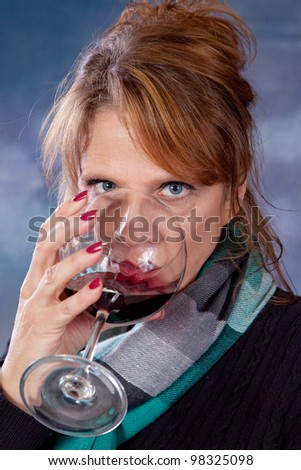 Mature woman drinking a glass of red wine