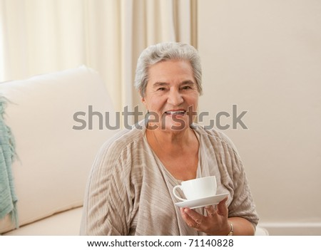 Mature woman drinking some tea - stock photo