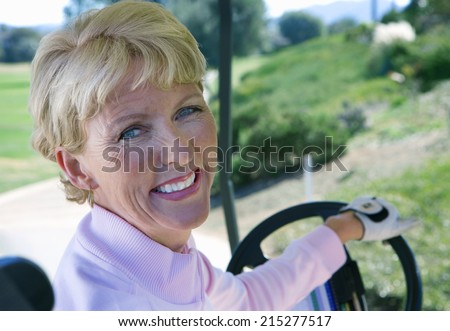 Mature woman driving golf buggy on golf course, looking over shoulder, smiling, close-up, rear view, portrait