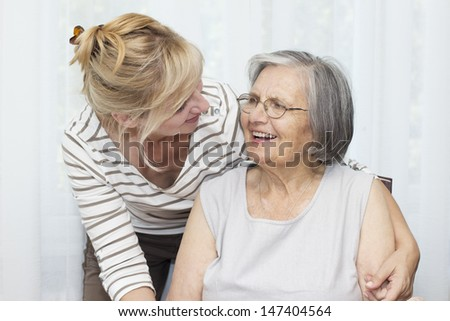 Mature woman embracing her senior mother. - stock photo