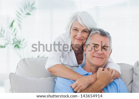 Mature woman embracing husband who is sitting on the couch - stock photo