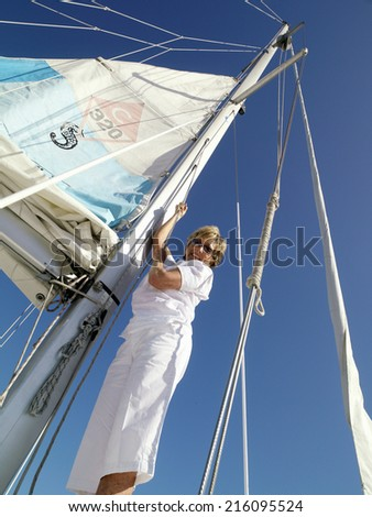Mature woman erecting sail on boat, smiling, portrait, low angle view
