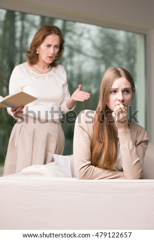 Mature woman exhorting the girl teenager sitting on a sofa