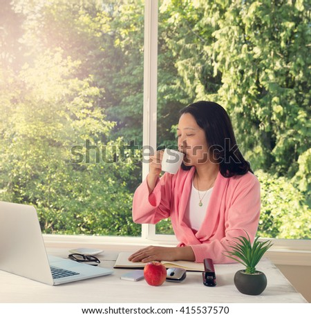 Mature woman, eyes closed, enjoying her morning coffee while working from home in front of large daylight window. Light haze effect applied to image.  - stock photo