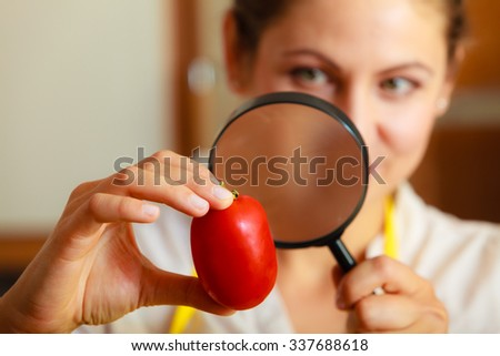 Mature woman female inspecting testing tomato food with magnifying glass. - stock photo