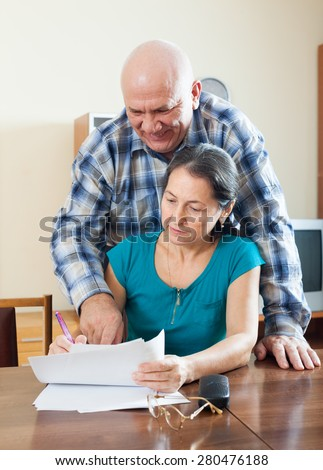 Mature woman fills documents, smiling man helps her at home - stock photo