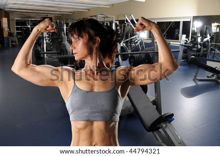Mature woman flexing muscles at the gym