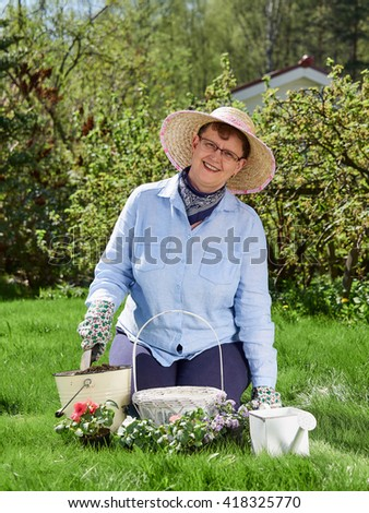 Mature woman gardening, she planting flowers