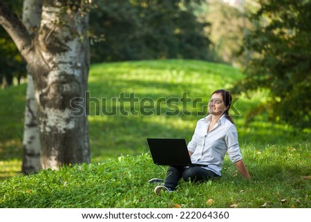 Mature woman happy on laptop sitting on the grass in the park - stock photo