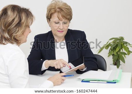 Mature woman having a meeting with financial adviser in the office. - stock photo
