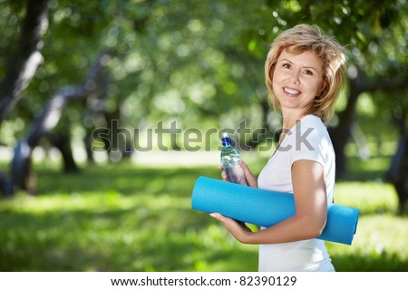 Mature woman in a park with a bottle and gym mat - stock photo