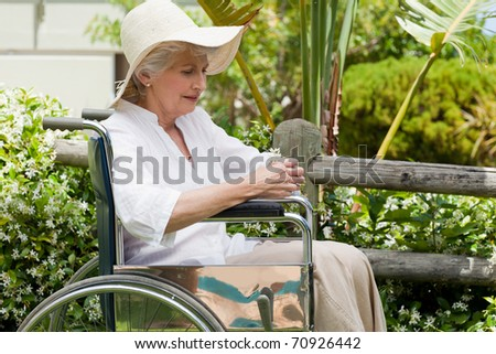 Mature woman in her wheelchair in the garden - stock photo