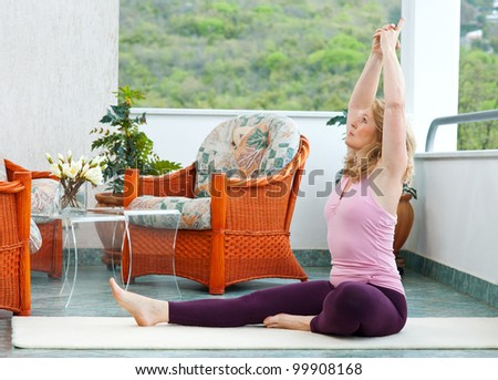 mature woman in relaxation stretching position on her balcony floor