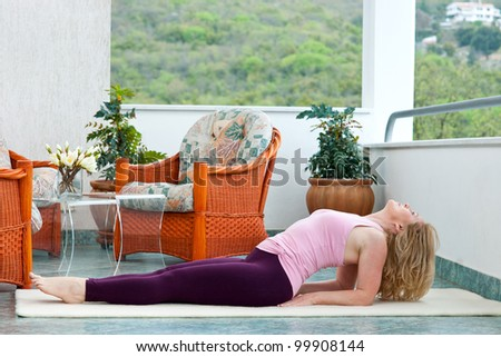 mature woman in relaxation yoga position on her balcony floor