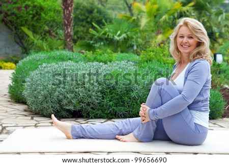 mature woman in relaxation yoga position outside in the garden - stock photo