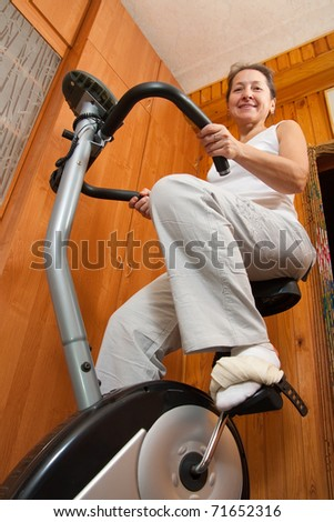 Mature woman in  sportswear exercising on exercise bike - stock photo