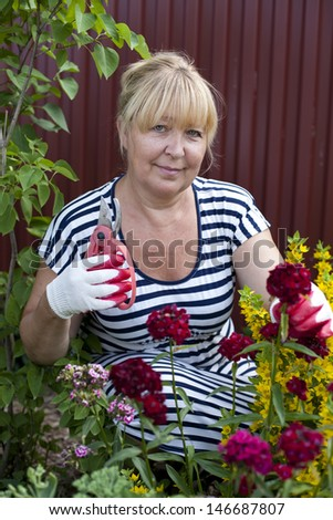 Mature woman in the garden, holds shears in one hand and is about to cut a flower