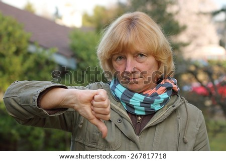 Mature woman in the suburbs with a frown and making a thumb down sign. - stock photo