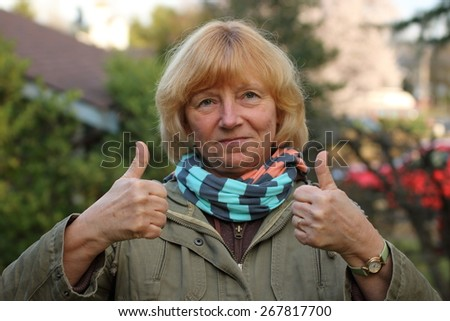 Mature woman in the suburbs with a smile and making a two thumbs up sign. - stock photo
