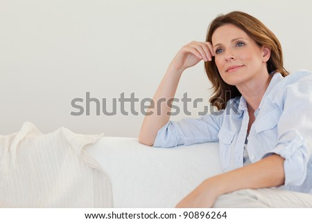 Mature woman in thoughts on the couch - stock photo
