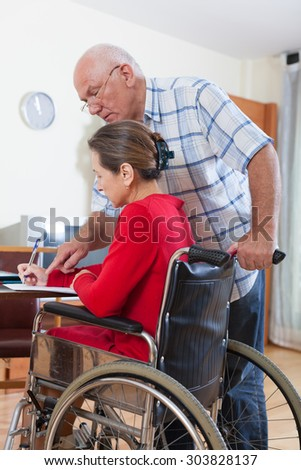 Mature woman in   wheelchair and   elderly man near .