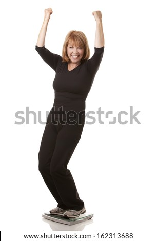 mature woman is standing on weight scale white background - stock photo
