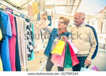 Mature woman looking clothes at market - Senior couple with shopping bags walking and buying some dresses to renew wardrobe - stock photo