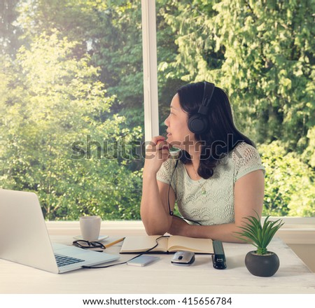 Mature woman, looking out window while holding apple in hand, working at home during bright morning daylight. Light effect applied to image.