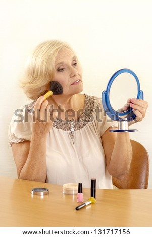 mature woman makes her makeup over light background