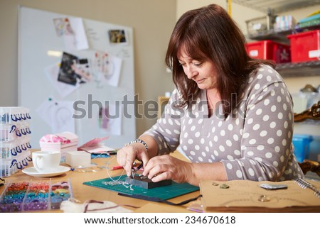 Mature Woman Making Jewelry At Home - stock photo