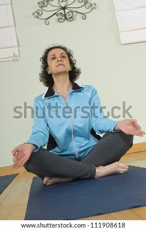 Mature woman meditating in lotus position - stock photo