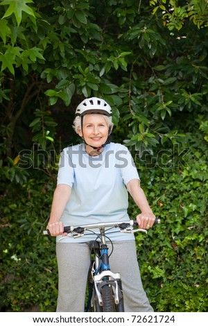Mature woman mountain biking outside - stock photo