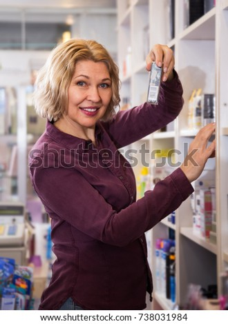 mature woman offering cream in the store cosmetics