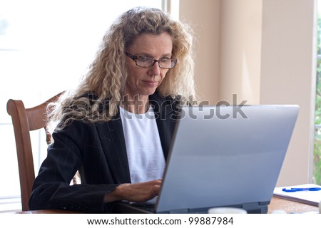 Mature woman on laptop working and typing - stock photo