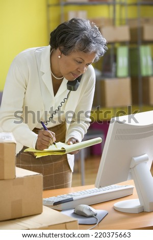 Mature woman on phone looking at computer screen and writing on legal pad