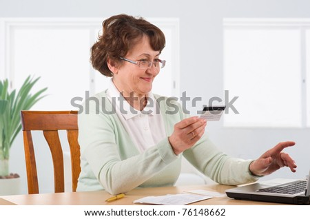 mature woman online banking, holding credit card - stock photo