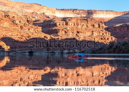 Mature woman paddling glass calm Green River in Stillwater Canyon - stock photo