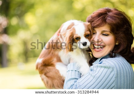 Mature woman playing with her cavalier dog outdoor in park - stock photo