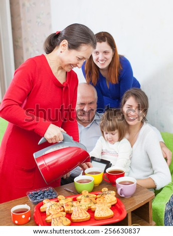 Mature woman pours tea from teapot for three generations family
