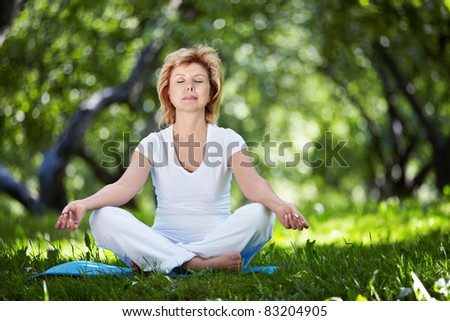 Mature woman practices yoga in the park - stock photo