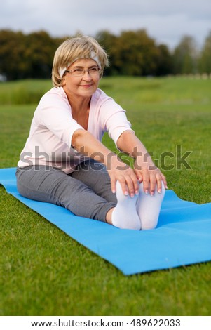 Mature woman practicing yoga in evening in the park