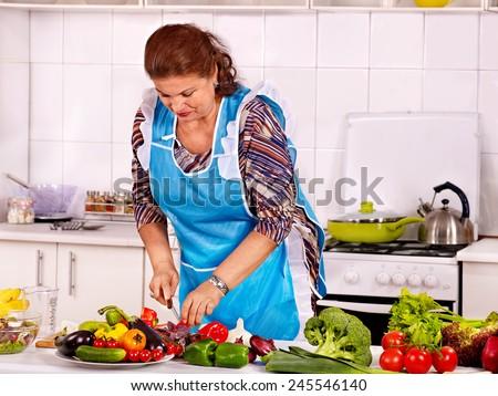 Mature woman preparing food at kitchen. - stock photo