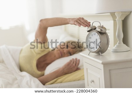 Mature woman pressing button of alarm clock while lying in bed at home - stock photo