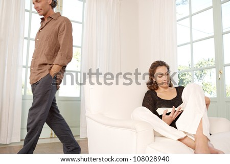 Mature woman reading a book at home while man is walking by. - stock photo