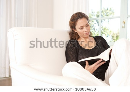 Mature woman reading a book while sitting on a white armchair at home.