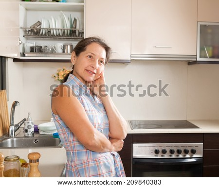 Mature woman relaxing at brightly kitchen