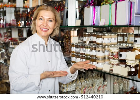 Mature woman selling gifts of fine chocolates and confectionery