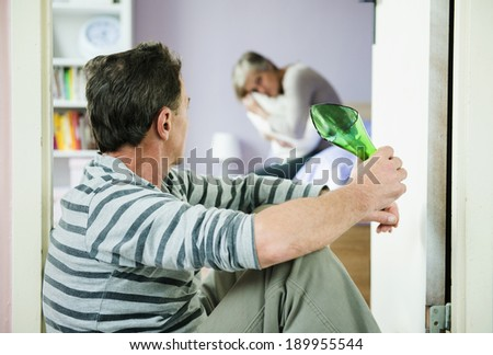 Mature woman siiting on the bed is scared of a man. Woman is victim of domestic violence and abuse. - stock photo